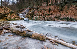 Frozen waterfall in forest. Frozen waterfall on the  river among forest. old brown foliage on the ground Stock Photos