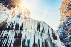 Frozen waterfall in the mountains at sunset. Royalty Free Stock Image