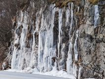Frozen waterfall plunging from a steep rock cliff royalty free stock photo