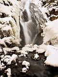 Frozen waterfall. Winter creek, icy stones and branches Stock Image
