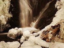 Frozen waterfall. Winter creek, icy stones and branches Royalty Free Stock Photos