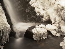 Frozen waterfall. Winter creek, icy stones and branches Stock Images
