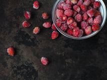 Frozen wild strawberry in bowl and scattered berries Royalty Free Stock Photography