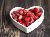 Frozen wild strawberry in a white bowl in the shape of heart Stock Image