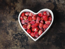 Frozen wild strawberry in a white bowl in the shape of heart Stock Photo
