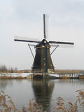 Frozen windmill. Historic windmill over frozen water during winter in Kinderdijk, northern Holland Royalty Free Stock Photo