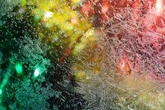 Frozen window. Christmas lights Royalty Free Stock Image