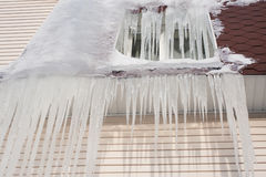 Frozen window. Icicles downspout on the brown roof. Cold weather concept. Stock Image