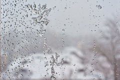 Frozen window  after the winter thaw. Stock Photography