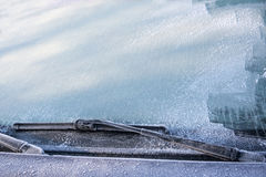 Frozen windscreen and windshield wipers totally covered with ice, caution, poor view causes dangerous driving im winter, traffic b Stock Photos