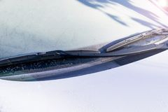 Frozen windshield wiper and glass on car. Frozen windshield. Frozen white car in winter. Ice on front window of a car Royalty Free Stock Image