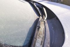 Frozen windshield wiper and glass on car. Frozen windshield. Frozen white car in winter. Ice on front window of a car Royalty Free Stock Photos