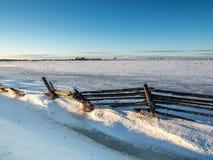Frozen Winter Snow Cedar Rail Fence. Country farm field in winter snow frozen landscape Royalty Free Stock Photo
