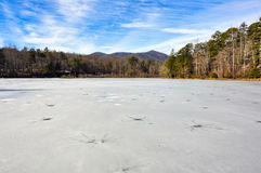 Frozen wintry landscape of cracked ice full of holes at Lake Powhatan in North Carolina. Lake Powhatan is completely frozen over with ice during a cold winter in Stock Photo