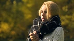 Frozen woman in autumn park feeling cold, warming hands, angina disease risk. Stock photo royalty free stock image