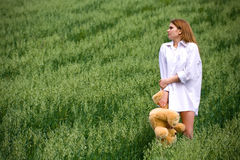 Frozen woman with a bear in grass Royalty Free Stock Photos