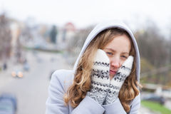 Frozen woman heated by mittens and a from hood Royalty Free Stock Photography