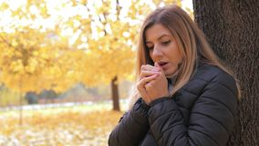 Frozen Woman Standing In The Autumn Street At The Tree Warms Her Hands Breathing. Young caucasian woman stands outdoor in the autumn park by tree. She was very royalty free stock photography