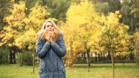 Frozen woman waiting for friend in autumn park, late for meeting, anticipation. Stock photo stock photo