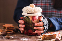 Frozen woman warm her hands with hot tea. Closeup of female hands in gloves holding glass jar with natural drink decorated with knitted cover Royalty Free Stock Photo