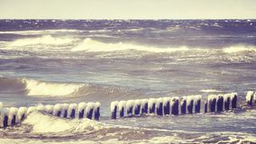 Frozen wooden breakwater on a windy day. Frozen wooden breakwater on a windy day, Baltic Sea in Poland, color toned picture Stock Photos