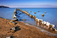 Frozen wooden breakwaters line. At Baltic Sea in Poland Stock Photography