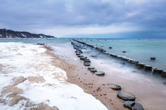 Frozen wooden breakwaters line to the world war II torpedo platform at Baltic Sea Stock Image