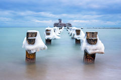 Frozen wooden breakwaters line to the world war II torpedo platform at Baltic Sea Stock Images