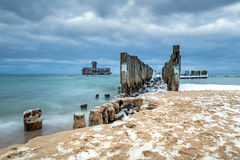 Frozen wooden breakwaters line to the world war II torpedo platform at Baltic Sea. Babie Doly, Poland Stock Photography