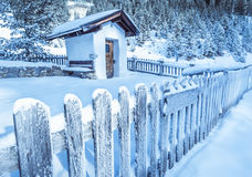 Frozen wooden fence and rustic chapel Stock Images