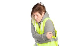 Frozen worker. A woman with a reflective vest is shaking like a leaf Stock Image