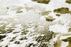 Frozen yellow water and wave covered with ice and snow abstract stock image