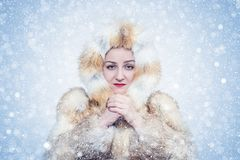 Frozen young woman in a fox fur coat, cold, snow, frost, blizzard stock photo