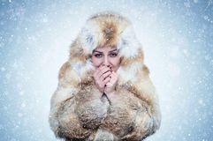 Frozen young woman in a fox fur coat warming hands, cold, snow, frost, blizzard royalty free stock image
