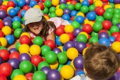Frère et soeur jouant dans une piscine de boule Photo stock