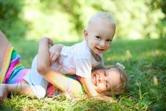 Frère et soeur jouant sur l'herbe Photos stock