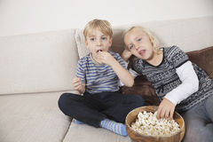Frère et soeur regardant la TV et mangeant du maïs éclaté Photo stock