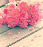 Försiktiga rosa rosor på trätabellen Fotografering för Bildbyråer