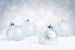 Försilvra julstruntsaker på snö med en silverbakgrund Royaltyfri Fotografi
