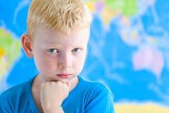 Förskole- pojke som drömmer i fron av världskartan Fotografering för Bildbyråer