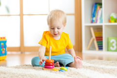 Förskolebarnbarn som spelar med den färgrika leksaken Lura att spela med den bildande träleksaken på dagis- eller daycaremitten L Royaltyfria Foton
