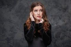 Förskräckt förvirrad ung kvinna som biter hennes kant Fotografering för Bildbyråer