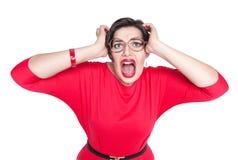 Förskräckt skrika som är härligt plus formatkvinna i den isolerade röda klänningen Arkivbilder