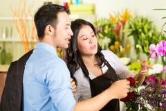 Försäljare och kund i blomsterhandel Royaltyfria Bilder