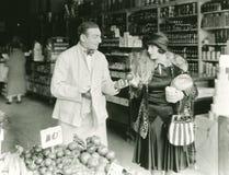 Försäljare som köpslår med kvinnan på marknaden Arkivfoto