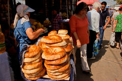 Försäljare som säljer traditionellt centralt asiatiskt bröd på den populära Oshen, marknadsför i Bishkek Royaltyfri Fotografi