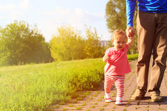 Första steg av lilla flickan med farsan i parkera Royaltyfria Foton