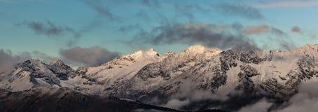 Första strålar av en resningsol är det högt i berg Arkivfoto