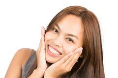 Förtjusande asiatiska flickahänder som kuper att le för framsida Royaltyfri Fotografi