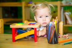 Förtjusande barnflicka som spelar med bildande leksaker i barnkammarerum Unge i dagis i Montessori förskole- grupp Royaltyfria Bilder